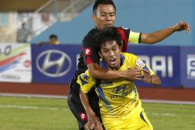 TOUGH TUSSLE: Tampines' Firdaus Idros (in yellow) being held back by DPMM captain Rosmin Kamis during their 1-1 draw in August.