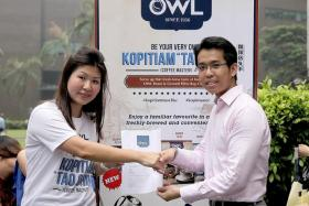 COFFEE LOVER: OWL brand manager Joie Wong shakes hands with the winner of the TNP-OWL giveaway, Mr Kua Khim Siang.
