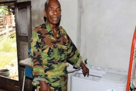 UNWANTED: Mr Zainol Hamid pointing to the washing machine in his house where the baby was found.