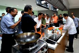 Mr Loo Tiong Bin (right) teaching a class of 18 men how to cook Hainanese pork chop on a weekday evening in a cooking class just for men.