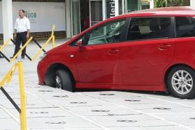 DAMAGED: Capitol Singapore workers using boards to cover the hole at the fountain area caused by a car driving over it.