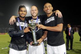 Johor Darul Takzim (JDT) players (from left) Hariss Harun, Luciano Figueroa and Marcos Antonio lifting the AFC Cup.