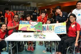 PAINTING A NEW LANDSCAPE: MCCY minister Grace Fu (fourth from left) interacting with para-athletes swimmer Yip Pin Xiu (right) and sailor Yap Qian Yin (third from right), and Singapore Disability Sports Council president Dr Teo-Koh Sock Miang (second from right) at the Team Singapore camp yesterday.