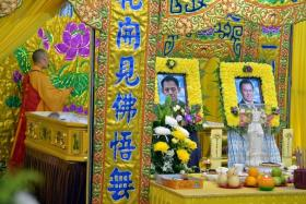 SLASHED: A monk performing a ritual at the wake of the Kovan murder victims, Mr Tan Boon Sin and his son Tan Chee Heong, at the Teochew Funeral Parlour on Ubi Road 4 on July 14, 2013.