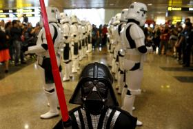 "Wesley Poh, a 5-year-old child dressed as Darth Vader, who came with his parents to visit the ""Star Wars"" exhibits, leads a group of Stormtrooper actors as they march around Singapore's Changi Airport on Thursday (Nov 12)."