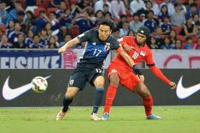 """""""We must keep our heads together and work hard for the next game. I believe we can get a result against Syria."""" - Lions striker Fazrul Nawaz (in red, losing out to Makoto Hasebe)"""