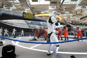 THE FACEOFF: Stormtroopers and X-Wing pilots stage a mock battle around the replica of the starfighter at Changi Airport.