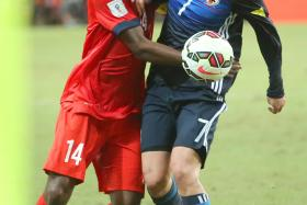 UP CLOSE AND PERSONAL: Lions midfielder Hariss Harun (left) tussles with Japan's Yosuke Kashiwagi.