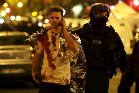 A French policeman assists a blood-covered victim near the Bataclan concert hall following attacks in Paris, France.