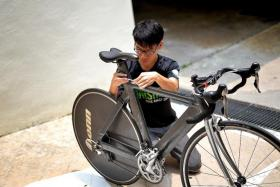 HANDY: Mr Chua Sheng Chuan shows how he fits the bicycle seat into the frame (above), using a machine he designed to cut bicycle parts.