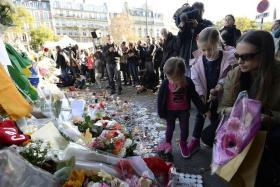 GRIEVING: People place flowers and candles near the Bataclan concert hall where more than 80 people were killed in Friday's attack.