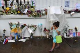 IN SINGAPORE: A little girl walks past the messages and flowers left in tribute to the victims of the Paris terror attacks outside the French Embassy in Singapore.