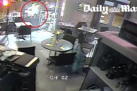 A screen grab of a CCTV footage allegedly showing Salah Abdeslam (circled) pointing his rifle at a woman.
