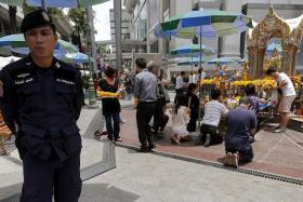 PRAYER: A police officer standing guard at the Erawan Shrine where two bimbs killed 20 people and injured 125 others in August.