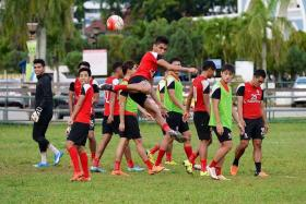 SAFUWAN STUNNER: LionsXII utility player Safuwan Baharudin surprising some of his teammates with a mid-air kick during training on a public field in Kuantan yesterday.