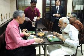 SUPPER: The two prime ministers and Mrs Lee (blocked) enjoying a meal at Komala Vilas restaurant. A female interpreter is seated behind Mr Modi.