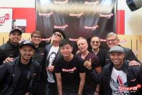 WINNER: Steven Chew (centre, in black T-shirt) won a contest to meet his idols Joe Elliot (fourth from left), Phil Collen (sixth from left), and Vivian Campbell (seventh from left) of Def Leppard when they were at the ONE FM 91.3 studio for an interview with the #1 Breakfast Show team.