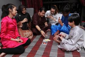 FAMILY: Mr Fahmi Rais with a photograph of his adoptive parents, who died more than 20 years ago. (Above) Mr Fahmi, 47, and his family, (from left) daughter Nur Natasya, 16, wife Madam Sulaimah Abdul Kadir, 40, daughter Nur Miskiah, 19, son Mikhael, 15, and son Reizuan, six.