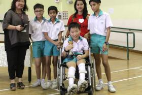 WINNERS, ALL: Keith Tan (in wheelchair) surrounded by (from left) form teacher Mrs Wendy Ng, best friends Fang Zheng Hao, Joven Christopher Arnold, his domestic helper Miss Rima Kartika, and Ethan Lai.