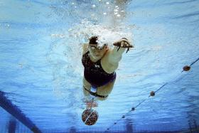 MIND OVER MATTER: Singapore para-swimmer Theresa Goh dragging a bucket under water over a distance of 25m as part of resistance training.