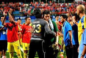 AND IT IS GOODBYE: LionsXII goalkeeper Izwan Mahbud (In green) hugging Pahang's Nasril Nourdin, as the Malaysia Cup champions form a guard of honour for the Singapore side after the game.