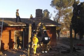 RESCUE EFFORT: Firefighters and sheriff officers at the chimney where the suspected burglar got stuck.