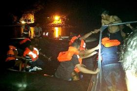 SCRAMBLE: The alarm was sounded and crew members shouted for passengers to put on their life vests. (Above) Passengers being transferred from a life raft onto boats.