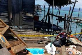 ACCIDENT: The damage done to a stilt house off Pulau Bum Bum in Sabah, after a homemade fish bomb accidentally went off while a sea gypsy family was constructing it.