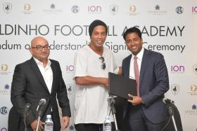 AGREEMENT: Ronaldinho sealing the deal with Tampines Rovers chairman Krishna Ramachandra (right).