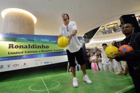 """""""Neymar is conquering his own space now and he has everything to be the greatest footballer in history."""" — Ronaldinho, who gave away seven autographed balls (above) after launching his e-scooter"""