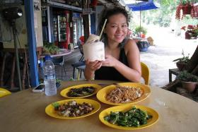 HUMBLE FARE: Inch Chua, who can break open coconuts with a parang, dining at one of her favourite restaurants on Pulau Ubin.