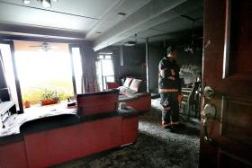 DAMAGE: (Left) The fire, which was believed to have originated from an air-conditioning unit, left the living room covered in soot. Police locking up the flat, which the SCDF had to force their way in to fight the fire.