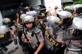 Indonesian riot police prepare to secure the premises following clashes inside Kerobokan prison on Bali.