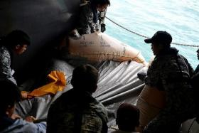 TEAMWORK: Crew from the RSS Persistence pulled out what looked like an aircraft's life raft from the Java Sea on the morning of Jan 4.