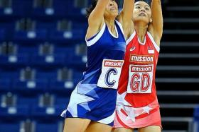 ON FORM: Singapore's Micky Lin (in red) fighting for a loose ball with Singapore Invitational's Vanessa Lee.