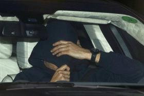 GONE: Jose Mourinho covering his face under a hood as he is driven out of Chelsea's training centre in Cobham on Thursday.