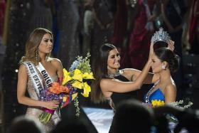 BLUNDER: After host Steve Harvey revealed he had mistakenly announced Miss Colombia Ariadna Gutierrez-Arevalo (in silver gown) as the winner, Miss Universe 2014 Paulina Vega (in black) removes the crown and places it on the head of Miss Philippines Pia Alonzo Wurtzbach (in blue).