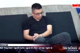 RAIDED: A screenshot of a Vietnamese TV new report showing Mr Lawrence Wong in handcuffs.