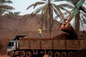 RED GOLD: A truck driver watching over an excavator loading his vehicle at a bauxite storage site in Pahang.