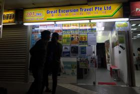 The exterior of 707-Inc Great Eastern Travels at Golden Mile Complex.They have resorted to printing posters telling people that they have not closed down