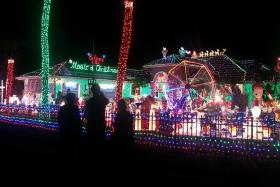 Visitors view the massive light display set up in the home of Mark and Kathy Hyatt in Plantation, Florida.