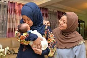 HAPPINESS: Madam Suhaidah Mamat holding baby Akmal Muaz as her neighbour Aminah Ismail looks on.