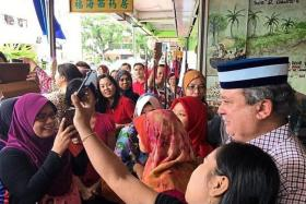 ON THE GROUND: Sultan Ibrahim Sultan Iskandar posing for a wefie with members of the public.