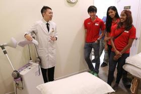 NEW PARTNERSHIP: National athletes (in red, from left to right) Soh Rui Yong, Dipna Lim-Prasad and Veronica Shanti Pereira touring the newly opened local traditional Chinese medicine company Kin Teck Tong at the Kallang Wave Mall. Singapore Athletics and the TCM company signed a one-year deal yesterday.
