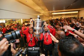JUBILATION: Fans celebrating the LionsXII's triumphant return after winning the Malaysian FA Cup  (above) in May. Three weeks later, The New Paper feted the Lions and goalkeeper Izwan Mahbud's heroics in holding mighty Japan to a 0-0 draw in Saitama.