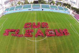 """LEAGUE OF THEIR OWN: Below, over 700 people, including S.League players, coaches, COE youth players and fans, form the words """"Our S.League"""" during the S.League Fanfare at Jalan Besar Stadium last year."""
