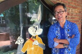 Mr Abdul Kadir Samin posing outside the shop where he works, Bugs Bunny Barber. Defence Minister Dr Ng En Hen has posted on his Facebook that Mr Abdul Kadir had cut his hair.