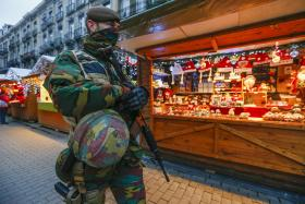 "A Belgian soldier patrols along ""Winter Wonders"", a Christmas market in central Brussels."
