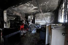 BURNED: Mr Tan Lai Chuan examining the aftermath of a fire that destroyed his flat's living room (above).