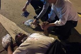 HELP CAME FAST: Mr Chen and Dr Liew aiding the injured man, who was bleeding from a cut on the back of his head.